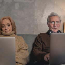 Eldery man and women sitting on couch using laptop